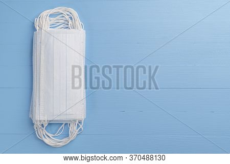 Stack Of Medical Protective Masks On A Light Blue Wooden Texture Background. Copyspace