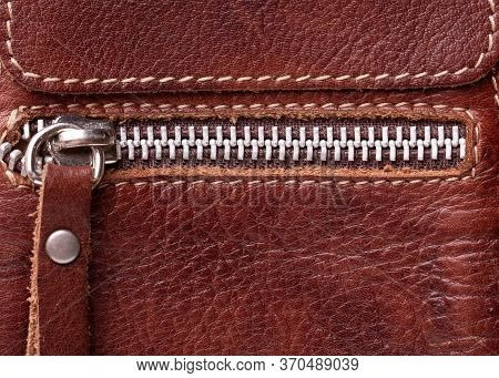 A Fragment Of Leather And Zipper Close-up. A Metal Zipper And A Brown Fragment Of A Leather Product.