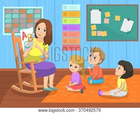 Teacher Holding Paper With Letter, Kids Sitting On Floor And Listening, Elementary School. Pupils Le