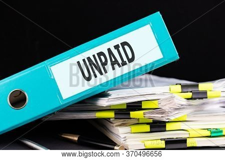 Text, Word Unpaid Is Written On A Folder Lying On Documents On An Office Desk. Business Concept.