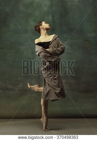 Warm. Graceful Classic Ballerina Dancing, Posing Isolated On Dark Studio Background. Stylish Trench