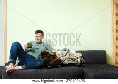Happy Handsome Man Sitting On The Couch At Home With Pet Dog Labrador Retriever Lying On His Knees,