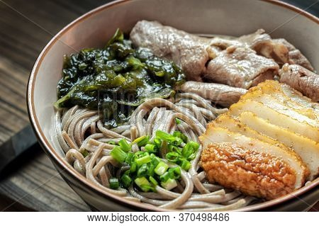 Japanese Soba Soup Noodles Served With Seaweed, Fish Cake, Pork Slices And Green Onions