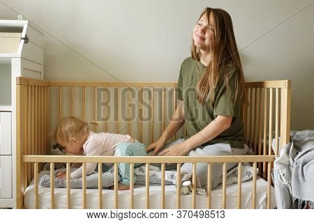 Young Tired Mother In Casual Clothes Sitting Together Wih Her Baby Girl In A Cot, Real Motherhood