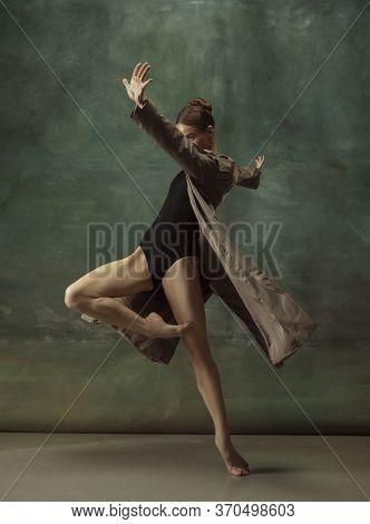 Warm. Graceful Classic Ballerina Dancing, Posing Isolated On Dark Studio Background. Stylish Trench