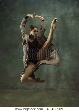 In Flight. Graceful Classic Ballerina Dancing, Posing Isolated On Dark Studio Background. Stylish Tr