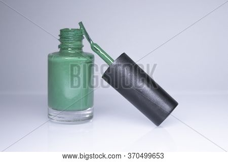 A Bottle With Spilled Green Nail Polish On White Background. Nail Lacquer. Nail Manicure Concept. Is