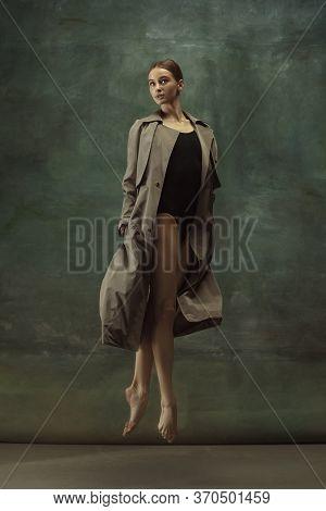 In Flight. Graceful Classic Ballerina Dancing, Posing Isolated On Dark Studio Background. Stylish Tr