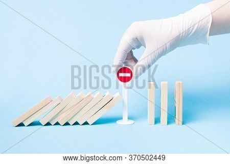 Hand In A White Medical Rubber Glove Stops A Domino From Falling Using A Plastic Toy Miniature Stop