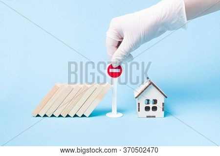 Hand In A White Medical Rubber Glove Stops A Domino Using A Miniature Stop Road Sign, Wooden House M