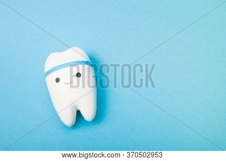 Happy Tooth On A Blue Background, Copy Space, Oral Care Concept, Toy Tooth Model, Pediatric Dentistr