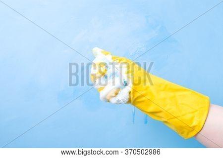 Hand In A Yellow Rubber Glove Squeezes A Wet Blue Sponge, Foam Spills From The Sponge, Blue Backgrou