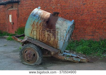 Old Rusty Tanker Truck Trailer On Brick Wall Background.