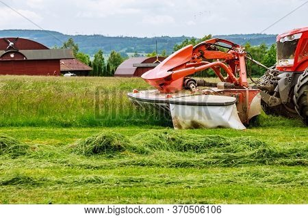 A Big Red Tractor Mows The Grass For Silage On The Field