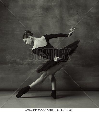 Art Motion. Graceful Classic Ballerina Dancing, Posing Isolated On Dark Studio Background. Elegance