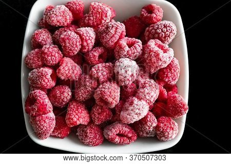 Frozen Ripe Raspberries In A White Deep Plate On A Black Background