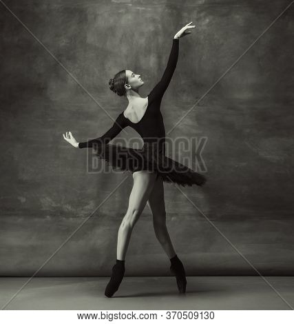 Passioned. Graceful Classic Ballerina Dancing, Posing Isolated On Dark Studio Background. Elegance B