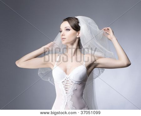 Portrait of young sexy bride over blue