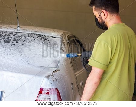 Man With Protective Mask Washing A Car