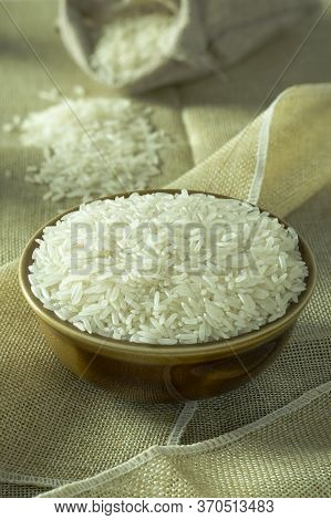 Uncooked Dry Thai Jasmine Rice In Bowl Is Isolated And Burlap Bag In Background Put On Brown Fabric,