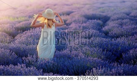 Romantic Lady On A Lavender Field Wears A Straw Hat. Beautiful Sunset, Sunrays Are Shining On Her Fa