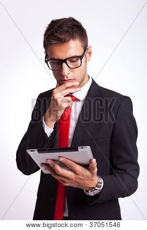 young business man is intrigued by the news he is reading onhis new tablet pad