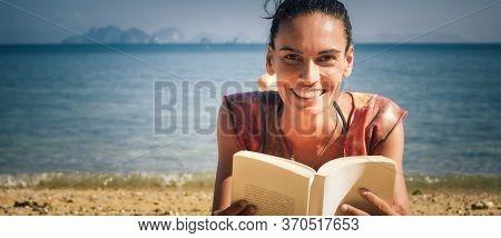 Woman Reading Book While Enjoying The Sunshine At The Beach. Koh Hong Island, Thailand