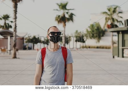Young Man In Grey T-shirt, Sun Glasses And With Backpack Wearing Black Protective Mask. Social Dista