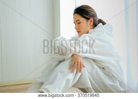 Beautiful Nurse Or Clinician With Body Protective Suit Sit Near Glass Window With Tire And Sad Emoti