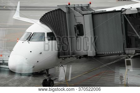 Plane On Airport Connected To Gate Sleeve. Aircraft And Sleeve. Gate At The Airport For Passengers T