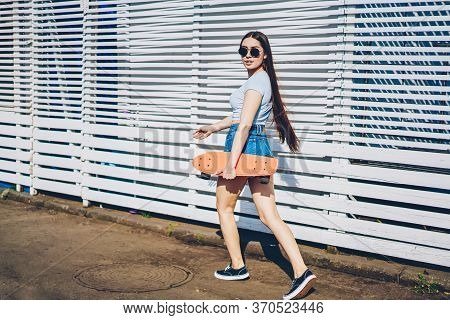 Positive Sportive Young Woman Strolling Near Publicity Area For Advertising
