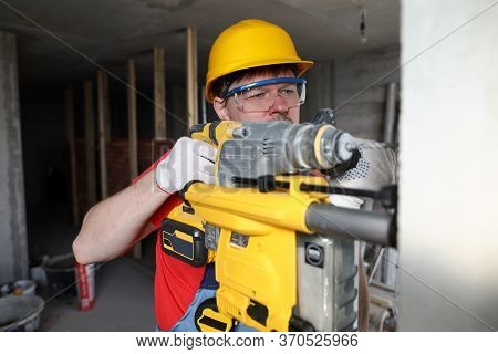 Builder In Helmet Holds Heavy Tool, Drills Wall. High Speed Drilling. Builder Efforts At Work. Abili