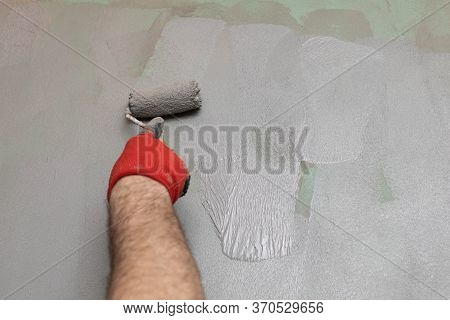 Close-up Of An Experienced Construction Worker Applying Damp Insulation With A Paint Roller On A Wal