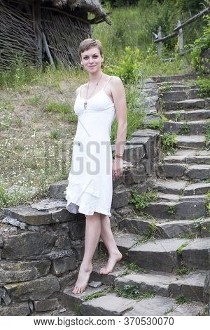 A Short-haired Girl In A White Linen Dress Is Standing Barefoot On Tiptoe On The Steps Of A Stone St
