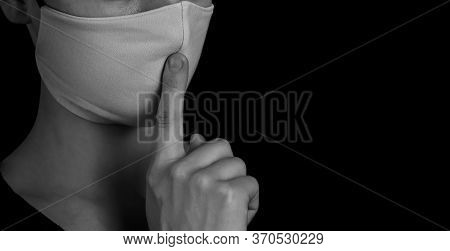 Black And White Portrait Young Woman In Protective Mask Showing Gesture Silence On Black Background,