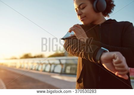 Close Up Of Female Runner Listening Music On Smartphone, Using Touchscreen On Armband, Running On Th