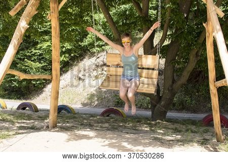 A Short-cut Girl In A T-shirt And Shorts, Swings On A Wooden Swing, Without Holding Her Hands And Ba