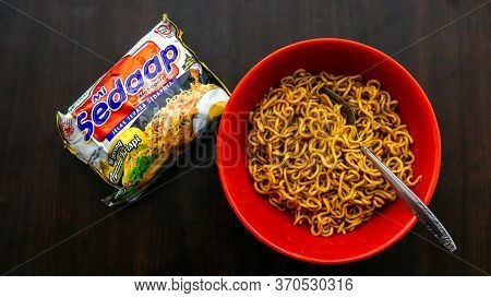 Cyberjaya, Malaysia - June 6, 2020: Top View Of Fried Instant Noodle Or Maggie With Fork In A Red Bo