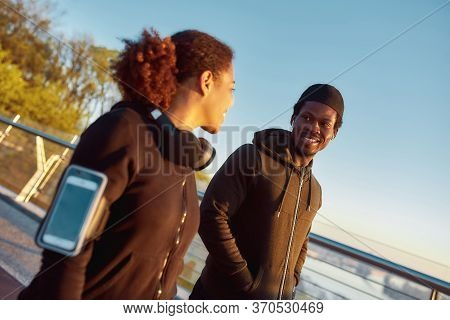 Happy African Male Athlet Talking With His Girlfriend And Smiling After Morning Jog. Couple In Black