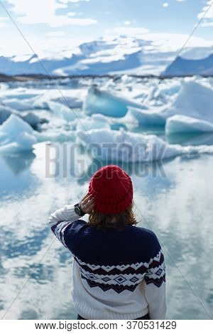 Rear View Of Female Tourist, Young Woman In Red Wool Hat Looking At Floating Ice In Jokulsarlon Glac