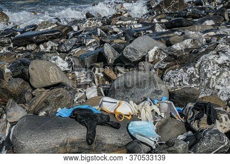 Medical Waste, Virus Mask And Plastic Gloves Garbage Discarded On Rocky Sea Coast, Coronavirus Covid