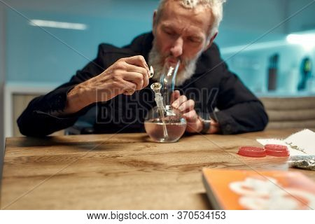 Senior Man Lighting Cannabis In The Bowl Of Glass Water Pipe Or Bong In The Kitchen. Marijuana Tools