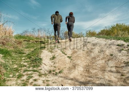 Back View Of African Fitness Couple In Sportswear Running Together Outdoors In Nature Or City Park.