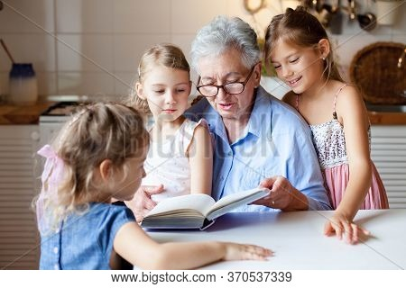 Reading Book At Home. Grandmother Reads Fairy Tale For Sisters. Kids Listen To Granny Story In Kitch