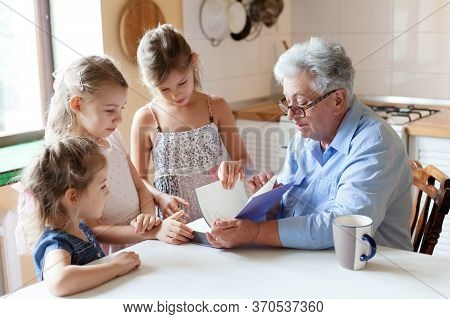 Reading Book At Home. Grandmother Teaching Girls. Kids Listen To Granny Fairy Tale In Cozy Kitchen.