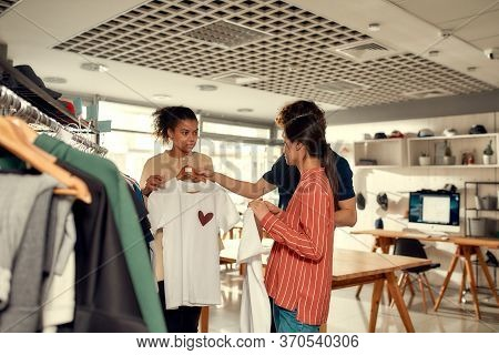 Creative People Looking At Already Made Items, While Discussing Logo And Design Of T-shirt. Young Ma