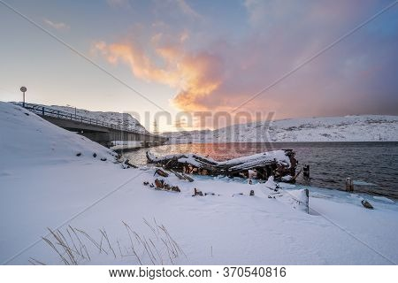 Old Wooden Shipwreck And Modern Concrete Bridge Over The Teriberka River At Sunset. Tourist Destinat