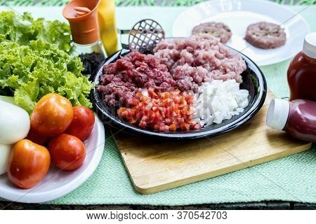 Homemade Hamburger With Beef Or Pork Meat With Lettuce And Cheese, Vegetables, Sauce And Placed On T