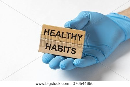 Healthy Habits Text Inscription On Wooden Blocks In Male Doctor Hands Isolated On White Background.