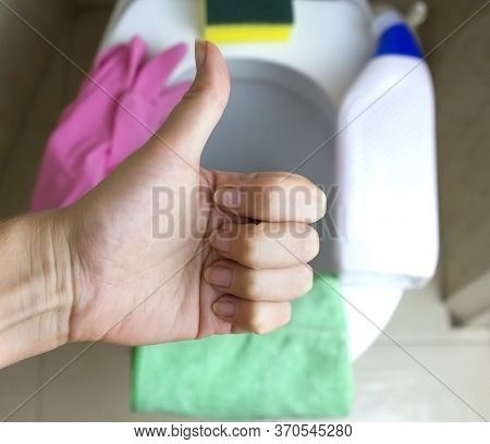 Close Up Female Hand Shows A Thumbs Up (cool) In The Toilet On The Background Of A Bottle Of Deterge